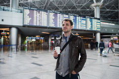 Young traveller man with coffee cup at the airport over board of departures and arrivals Royalty Free Stock Images