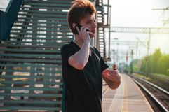 Young traveller man talking through the phone at the railway station during hot summer weather, making gestures while talking stock images