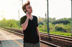 Young traveller man talking through the phone at the railway station during hot summer weather, making gestures while talking royalty free stock images