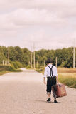 Young traveller walking away with suitcase Royalty Free Stock Images