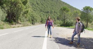 Young travellers hitch hiking on road. Young male and female travellers standing in sun light on road in mountains and hitch hiking stock video
