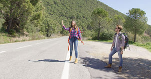Young travellers hitch hiking on road Stock Image