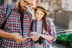 Young travellers stand side by side and look at tablet. Man holds it in hads. They are serious and concentrated stock photo