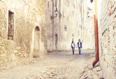 Young travelling couple having a medieval walk on an old street Stock Image