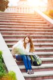 Young travelling woman sitting with map on stairs. In old european town Royalty Free Stock Image