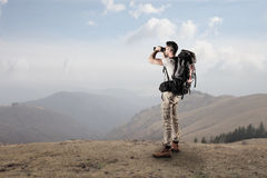Young trekking and looking through a binoculars. Young man doing some trekking in the mountains and using a binoculars Royalty Free Stock Photo