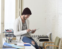 Young trendy businessman in beanie and cool hipster informal look sitting on home office desk using digital tablet pad happy Stock Photos