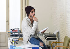 Young trendy businessman in cool hipster beanie and informal look writing on pad working thoughtful Royalty Free Stock Images