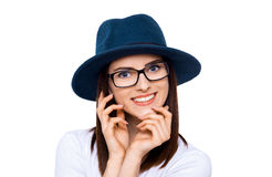 Young, trendy and and confident. A young woman in hat smiling at the camera against a white background Royalty Free Stock Image