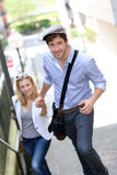 Young trendy couple climbing up stairs in town Stock Images