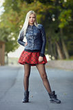 Young trendy dressed blonde lady showing her weekend outfit having fun and posing on park path shallow depth of field. Young trendy dressed blonde woman showing Stock Photo