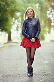 Young trendy dressed blonde woman demonstrate her weekend outfit posing on park path shallow depth of field Stock Image