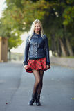 Young trendy dressed blonde woman showing her weekend outfit having fun and posing on park path shallow depth of field Royalty Free Stock Image