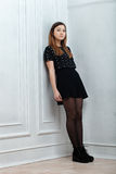 Young trendy dressed woman posing in black skirt boots tights shirt near white wall indoor Royalty Free Stock Photo