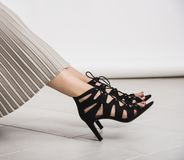 Young and trendy female legs with black high heeled shoes with heels on the ground. Studio abstract shot, body parts royalty free stock photos