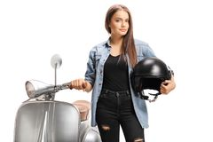 Young trendy female standing next to a scooter and holding a helmet royalty free stock image