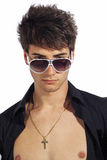 Young trendy guy. Italian man with big sunglasses and open black shirt. Young trendy guy. Big sunglasses and open black shirt. Gold necklace with crucifix. White Royalty Free Stock Image