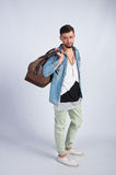 Young trendy guy in the studio is a travel bag Stock Images