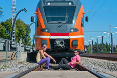 Young trendy guys in front of train Royalty Free Stock Image