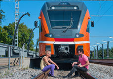 Young trendy guys in front of train. Young trendy guys sitting in front of train Royalty Free Stock Photo