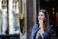 Young and trendy hipster woman is standing in the city, wondering what to buy. Royalty Free Stock Images