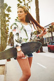 Young trendy long haired woman posing with her longboard enjoying good day in summer Royalty Free Stock Photography
