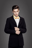 Young trendy man. Black suite, yellow bowtie, gray background. Portrait. Portrait of young trendy man in black suite with yellow bow-tie on gray background Royalty Free Stock Photos