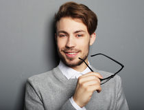 Young  trendy man with glasses smiling, studio shot Stock Photography