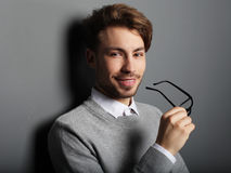 Young  trendy man with glasses smiling, studio shot Royalty Free Stock Photo