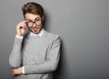 Young  trendy man with glasses smiling, studio shot Stock Photo