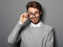 Young  trendy man with glasses smiling, studio shot Royalty Free Stock Images