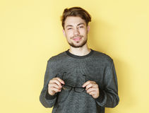 Young  trendy man with glasses smiling, studio shot Royalty Free Stock Photography