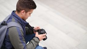Young trendy man listen to music on smartphone sitting on the steps outdoor stock video footage