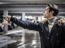 Confident man on parking setting alarm. Young trendy man in outerwear standing on parking using alarm remote control Stock Images