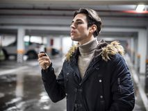 Confident man on parking setting car alarm. Young trendy man in outerwear standing on parking using alarm remote control Royalty Free Stock Photos