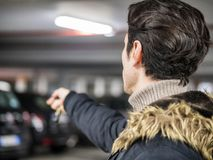 Confident man on parking setting car alarm. Young trendy man in outerwear standing on parking using alarm remote control Stock Photo