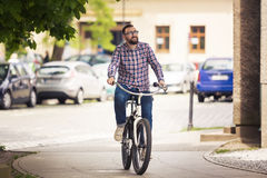 Young trendy man riding city bike on pavement. Portrait of young trendy man riding city bike on pavement Stock Image