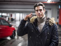 Confident man on parking setting car alarm. Young trendy man in winter outerwear standing on parking showing alarm remote control to the camera, smiling Royalty Free Stock Images