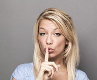 Young trendy woman asking to keep quiet for discretion Royalty Free Stock Image