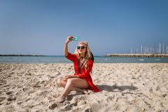 Young trendy woman in bright red dress makes a selfie on the background of sea stock image