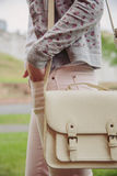 Young trendy woman holding white satchel bag Royalty Free Stock Photos