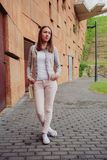 Young trendy woman over stone wall background. Fashion portrait of young trendy woman wearing gray jacket, pink jeans and white satchel bag over a stone wall Royalty Free Stock Photos
