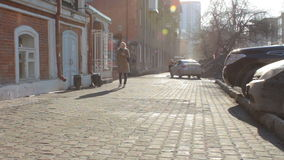 Young trendy woman with smartphone walking in the city at sunny day. Spring time. Young trendy blond woman with cellphone walking in the city at sunny day stock video footage