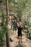 Young trial bikers carrying bikes on backs. At forest royalty free stock photography