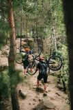 Young trial bikers carrying bikes on backs at forest. And going uphill stock image