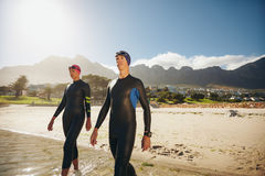 Young triathletes walking into the sea wearing wetsuit Stock Photography