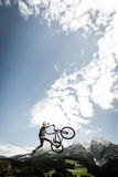 Young trick stunt biker jumps trick high Royalty Free Stock Image