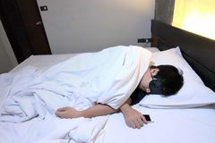 Young tried Asian man comfortable sleeping with mask on bed in bedroom at night.  Royalty Free Stock Photography