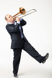 Young Trombone Player. Portrait of a young man playing his trombone on white Stock Photography