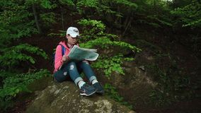 Young troubled tourist girl with backpack looking to her map and lifting up eyes checking with local terrain stock video